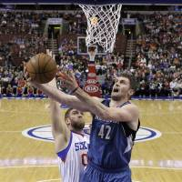 Big road win: Minnesota's Kevin Love goes up for a shot against Philadelphia's Spencer Hawes in the first half on Monday night. The Timberwolves beat the 76ers 126-95. | AP
