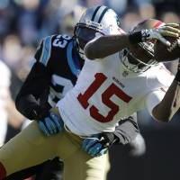 Safe and sound: San Francisco wide receiver Michael Crabtree makes a catch ahead of Carolina's Melvin White during the 49ers' 23-10 win in their NFC divisional playoff on Sunday. | AP
