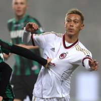 False start: AC Milan's Keisuke Honda challenges Sassuolo's Alessandro Longhi in his debut for the Rossoneri on Sunday. Sassuolo won the game 4-3. | AFP-JIJI