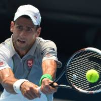 Expeditious victory: Novak Djokovic plays a shot from Leonardo Mayer in their second-round match at the Australian Open on Wednesday. Djokovic won 6-0, 6-4, 6-4.   AFP-JIJI
