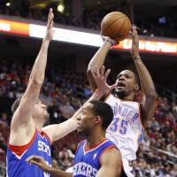 Didn't miss a beat: The Thunder's Kevin Durant shoots over Sixers defenders Spencer Hawes (left) and Evan Turner.   AP