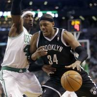 Back where it began: Nets forward Paul Pierce competes against the Celtics' Gerald Wallace on Sunday in Boston. Pierce was playing as a visitor against his former team for the first time. | AP