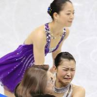 Differing emotions: Kanako Murakami is comforted by coach Machiko Yamada after her crucial performance in the short program at the Japan nationals, while Akiko Suzuki calmly takes the ice. | KYODO