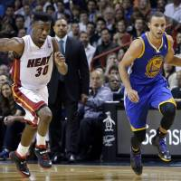 Major force: Golden State's Stephen Curry brings the ball upcourt against Miami in the second half on Thursday night. The Warriors downed the Heat 123-114. | AP