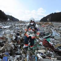 Once beyond imagination, yet now familiar: A rescue worker walks through detritus in the tsunami-hit town of Minamisanriku, Miyagi Prefecture, on March 18, 2011. | AFP-JIJI