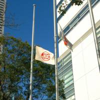 Remembering those lost: The company and the national flags are hoisted half-staff at JGC Corp. in Yokohama Thursday morning. | KYODO