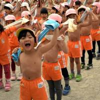In the pink: Kids towel off after exercising at a playground at Tokyo's Mizuho Kindergarten on Monday, the day on traditional Japanese calendars recognized as 'daikan' (major cold), or the chilliest day of the year. The 500 kindergartners play shirtless every day to stay healthy.   AFP-JIJI