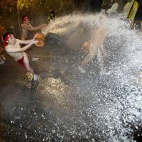 Brief return to childhood: Men wearing loincloths throw hot water at each other during the annual hot-spring water splashing festival held in Naganohara, Gunma Prefecture, on Monday. | KYODO