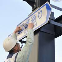 Foreigner-friendly direction: A worker covers a transliteration of a Japanese street name with its English equivalent on Wednesday in the city of Hiroshima. | KYODO