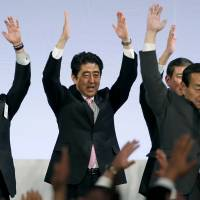 In the mood: Prime Minister Shinzo Abe and fellow Liberal Democratic Party members shout traditional 'Banzai (long life)' cheers during the party's annual convention at a hotel in Tokyo on Sunday. | AP