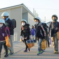 Taking precautions: Children in Hamamatsu, Shizuoka Prefecture, walk to their elementary school, which reopened Wednesday after being closed due to a mass norovirus outbreak. | KYODO
