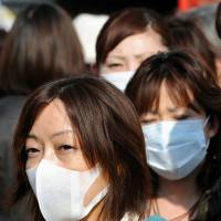 Pollen protection: Pedestrians wear face masks in Tokyo. | BLOOMBERG
