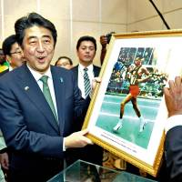 Sports legend: Prime Minister Shinzo Abe holds a photograph of Ethiopian marathon runner Abebe Bikila, presented to him by Bikila's son, in Addis Ababa on Monday. | AFP-JIJI