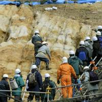 Digging deep: Experts from the Nuclear Regulation Authority examine the soil around reactor 2 at Tsuruga nuclear power plant in Fukui Prefecture on Monday.   KYODO