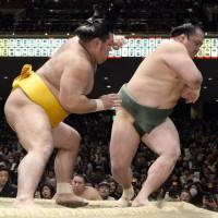 Forced to the edge: Masunoyama (left) takes care of business against Shotenro at the New Year Grand Sumo Tournament on Saturday. | KYODO