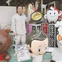 Attention grabbers: Masahide Nakamura, president of Pop Kougei Co., poses with some '3-D ads' his company created at his factory in Yao, Osaka Prefecture, on Dec. 6.   KYODO