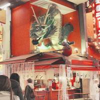 First of its kind: A green dragon sculpture, installed above a ramen shop in Osaka's Dotombori district, is the first so-called 3-D ad Pop Kougei Co. created, in 1997.   KYODO