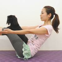 Dharma dog: Yoga instructor Ayu achieves a yoga pose called 'boat' with her Pekingese, Candy, on Dec. 21. | KYODO