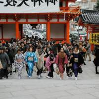 Participants in a January 2013 Kimono Jack event enter Kyoto's Yasaka Shrine while passers-by look on. | KYODO