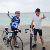 Cashing in: Toshiki Nishihata (right) of Recruit Career Co. poses with a colleague during their cycling tour of Okinawa, an excursion that was enabled by the company's new 'anniversary leave' system, which actually pays them to take their holidays. | KYODO