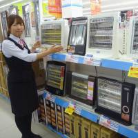 Keep it simple: A clerk at a Kojima electronics store in Setagaya Ward, Tokyo, points out popular low-priced 'no-brand' space heaters. | KYODO