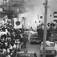 Fired up: Residents in the Okinawa city of Itoman wave Hinomaru flags as they cheer a local runner during the torch relay on Sept. 8, 1964, preceding the Tokyo Olympics held the next month.  | KYODO