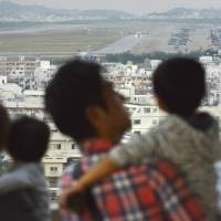 People last Dec. 5 look out over U.S. Marine Corps Air Station Futenma in Ginowan, also in Okinawa. | KYODO