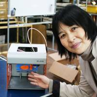 Bringing it home: Mariko Obayashi, president of Smile Link, shows off the company's 3-D printer for personal use in Ota Ward, Tokyo, in November. | KYODO