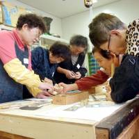 Brainstorming: A group of elderly women participate in a workshop for inventing tools for disabled people and seniors at Kitakyushu Technical Aid Center in November. | KYODO