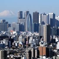 Concrete peaks: Mount Fuji, shown in December, provides a dramatic backdrop for the twin towers of City Hall and the dozens of other skyscrapers that have been erected on the west side of Shinjuku Station since the war. | SATOKO KAWASAKI
