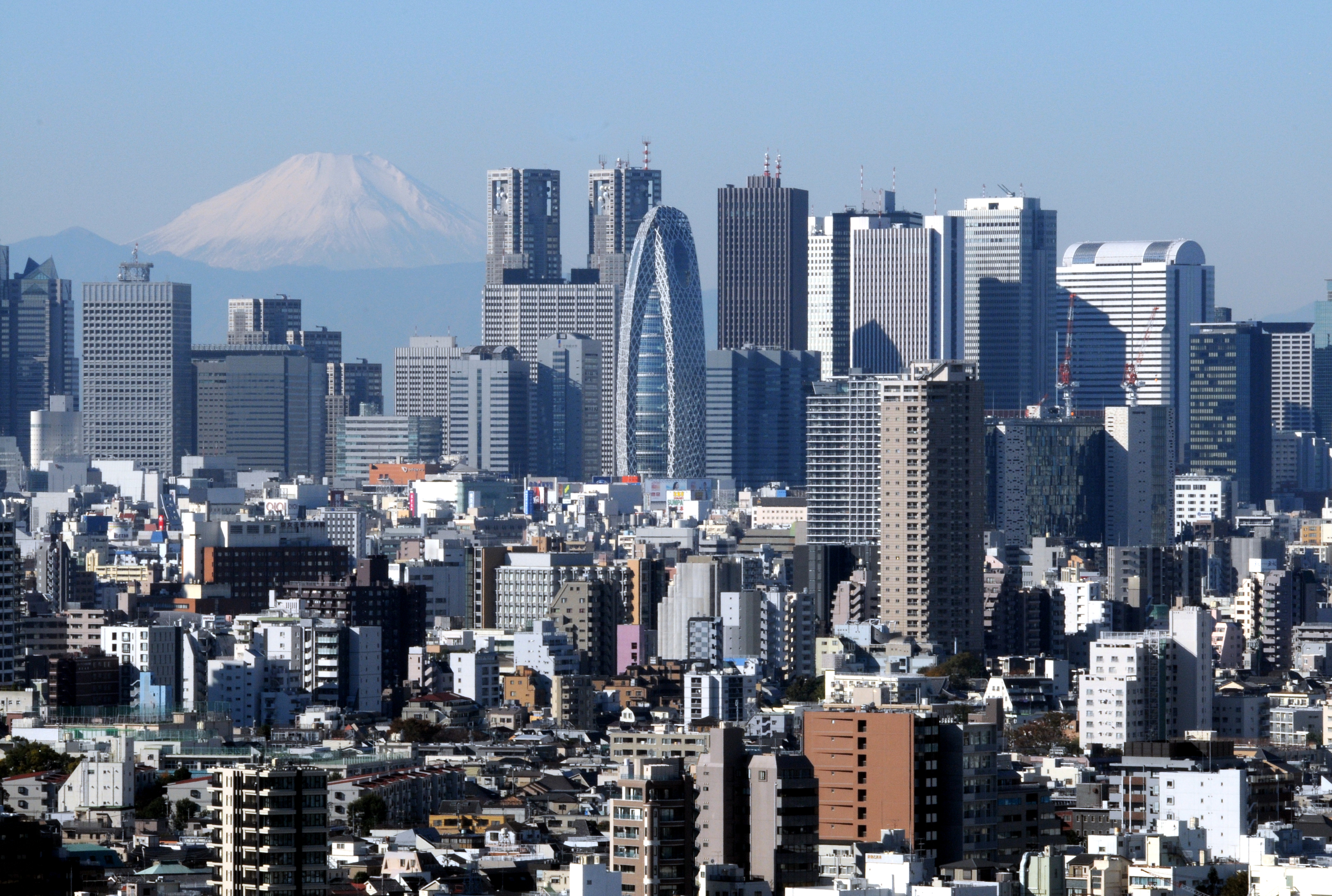 Concrete peaks: Mount Fuji, shown in December, provides a dramatic backdrop for the twin towers of City Hall and the dozens of other skyscrapers that have been erected on the west side of Shinjuku Station since the war.   SATOKO KAWASAKI
