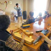 Strumming along: Residents of a nursing home operated by Maihama Club Co. in Urayasu, Chiba Prefecture, play easy-to-play musical instruments in December as part of a music therapy introduced from Sweden. | KYODO