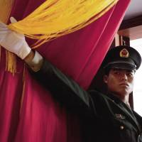 Going for gold?: A soldier with the Chinese People's Liberation Army beckons reporters during a July 2011 media tour in Beijing designed to make the PLA appear more transparent. | BLOOMBERG
