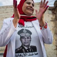 Supporter: A woman wears a T-shirt bearing a photo of Defense Minister Gen. Abdel-Fattah el-Sissi outside a Cairo polling station on Jan. 14, the first day of voting in Egypt's constitutional referendum. | AP