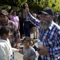 Turning the tables: Mexican self-defense group spokesman Estanislao Beltran waves to the people of Tancitaro on Thursday. | AP