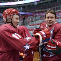 Sports icon: President Vladimir Putin touches the glove of former ice hockey star Pavel Bure after a friendly game in Sochi on Saturday between former hockey greats, including Soviet-era champion Alexander Yakushev. | AP