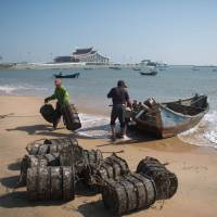 What's the catch?: Fishermen unload their boat at a beach on the island of Pingtan, in China's southeastern Fujian province, in October. | AFP-JIJI