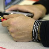 Honor roll: Oskar Zepeda wears a metal bracelet bearing the names of friends who died while serving with him during his nine tours of duty in Iraq and Afghanistan. | AP