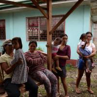 Behind closed doors: Filipinos in the Cebu village of Ibabao accompany their children to a day care center next to the now-abandoned house (rear right) that was used to stream live sex acts of children to pedophiles online overseas. | AFP-JIJI