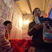Traumatized: Wu Yongyuan shows medicines his wife, Gong Qifeng (left), takes to control her schizophrenia symptoms in a Beijing room they rented while he petitions the central government for help. | AP