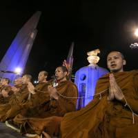 Ever mindful: Buddhist monks chant prayers and meditate at the Democracy Monument in Bangkok on Jan. 1. | AP