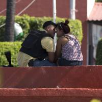 Keeping the peace: A man belonging to the Self-Defense Council of Michoacan kisses a woman in the main square of the town of Nueva Italia, Mexico, on Monday. | AP