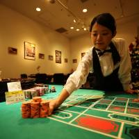 Place your bets: A dealer places chips on a roulette table at Casino Venus, a mock casino operated by Japan Casino School and Bright Inc. to simulate a real gambling experience, in the VenusFort shopping outlet in Tokyo on Dec. 3. | BLOOMBERG