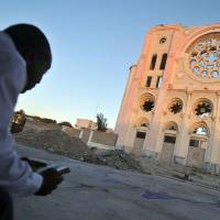 Praying for a miracle: A Haitian reads the New Testament in front of Port-au-Prince Cathedral, most of which was destroyed in the January 2010 earthquake, on Friday. | AFP-JIJI