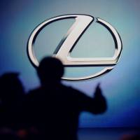 In the spotlight: The silhouettes of attendees arriving for a press conference are seen as the Lexus logo is displayed during the Detroit auto show on Tuesday.   BLOOMBERG