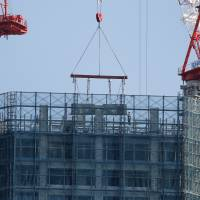 Making more: Workers labor on a residential building under construction in Tokyo on Nov. 22. Demand for industrial materials is showing clear signs of recovery, with steel and cement production in 2013 hitting their highest levels in five years. | BLOOMBERG