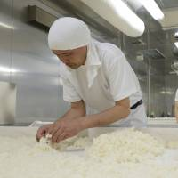 Workers spread steamed rice on tables to treat it with a mold called 'koji' in preparation for brewing. | BLOOMBERG