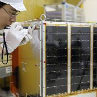 Can-do spirit: An Axelspace Corp. employee checks a micro-satellite in a clean room at the company's offices in Tokyo on Dec. 18.  | BLOOMBERG