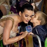Out of fashion?: U.S. singer Katy Perry receives a kiss from a boy after he presented her with a bouquet of flowers on the red carpet at a central London cinema for the European premiere of her film 'Part of Me' in July  2012. A pair of Perry's false eyelashes have been added to an exhibit on cheap fashion at Britain's Victoria and Albert Museum. | AP