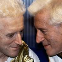 Look-alike: Jimmy Savile poses for a picture with his waxwork model at Madame Tussauds museum in London in December 1986. | AP